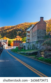 View of High Street in Harpers Ferry in West Virginia, USA with ancient Houses and  colorful Foliage on Trees in Background on a sunny Day