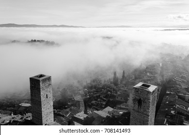 A view from an high tower in the little town of San Gimignano, tuscany italy. A sea made of fog until the horizon with light blue mountains in the background and a little town emerging from the mist