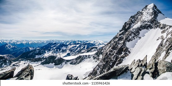 View of the highest austrian mountain Grossglockner. An alpine mountain landscape of High Taura with the summit of Grossgloner. Alpinist ascent route to the summit. Snow, rocks and sharp ridge.