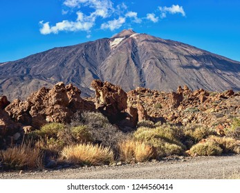 """View of the highest mountain of Spain, the """"Teide"""" with 3718 m altitude. A small snow-rest is near the top and in the foreground there are a few daisies and strawflowers."""