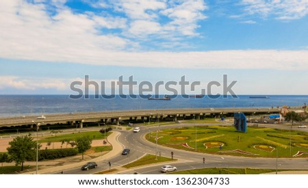View of a highway in Trabzon, Turkey with a sceneray background. Ships are in the black sea during a day with blue sky and clouds.