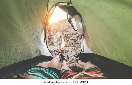 View of hikers couple inside tent camping in rock mountains with their dog - Sporty people relaxing after a trekking day with next fire at sunset Travel,love,nature and healthy concept - Focus on feet