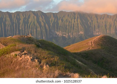 View of hikers on trail on Lanikai Pillbox hike in Kailua, Hawaii at sunrise.
