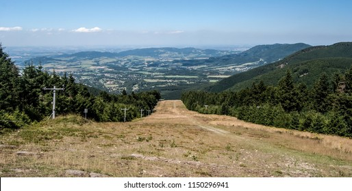 view from hiking trail between Radhost hill and Pustevny in Moravskoslezske Beskydy mountains in Czech republic with ski slope, countryside and hills during nice summer day