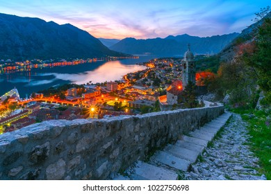 View from the hill to the Adriatic Mediterranean town and the picturesque bay at evening, night. The town in the mountains. Night city lights. Ancient Montenegrin town of Kotor.