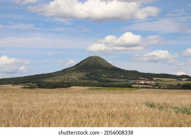 A view to the hill Oblik surrounded by fields and blue sky above near Louny, Czech republic