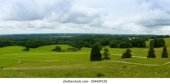 view from the hill on fields and the woods with footpaths