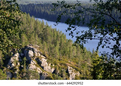 View from hill on rock face, forest and river. Finland
