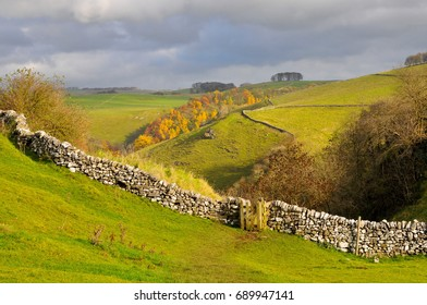 View of hills in Derbyshire, England, showing a path and gate on a walking trail.