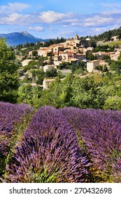 View of a hilltop village in Provence, France over beautiful rows of lavender