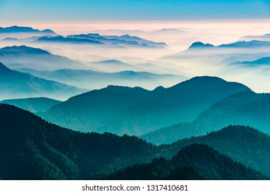 View of Himalayas mountain range with visible silhouettes through the colorful fog from Khalia top trek trail. Khalia top in himalayan region of Kumaon, Uttarakhand, India.
