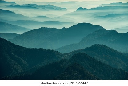 View of Himalayas mountain range with visible silhouettes through the colorful fog from Khalia top trek trail. Khalia top is at an altitude of 3500m himalayan region of Kumaon, Uttarakhand, India.