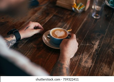 View of hipster man with authentic artisan tattoo hold cup of freshly brewed coffee with latte art heart made by barista, in blue cup at local cafe or bar, sits behind wooden aged table