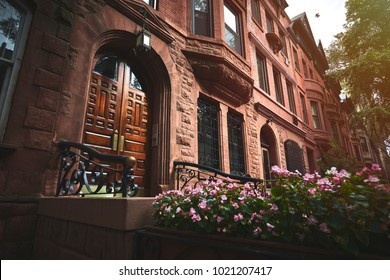 A view of a historic brownstone on a sunny summer day in an iconic neighborhood of Manhattan, New York City.