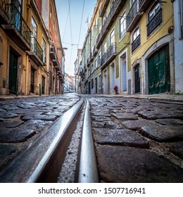 View of the historic city of Lisbon in Portugal with its cobblestone streets, ancient buildings, and tracks for the famous Tram28 trolley.