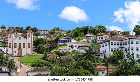 Blick auf die historische Bergbaustadt Serro auf einem Hügel, blauer Himmel und weiße Wolken, Minas Gerais, Brasilien