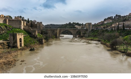 View of the historic Toledo bridge in Spain with the Tagus river in the center and centenary buildings on a winter afternoon