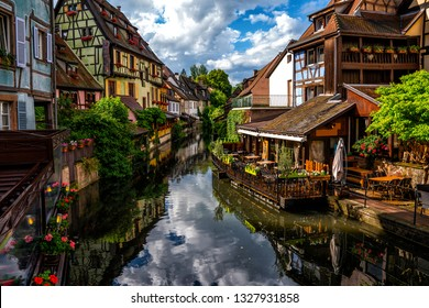 View of the historic town of Colmar, also known as Little Venice, with tourists taking a boat ride along traditional colorful houses on idyllic river Lauch, Colmar, Alsace, France