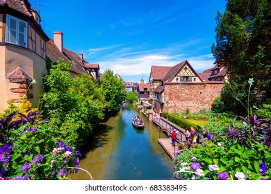 View of the historic town of Colmar, also known as Little Venice, with tourists taking a boat ride along traditional colorful houses on idyllic river Lauch, Colmar, Alsace, France on July 04, 2017