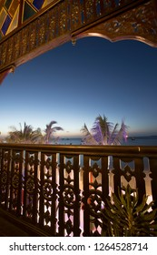 View from historic wodden balcony in late evening with womderful illuminated palmtrees and the ocen behind