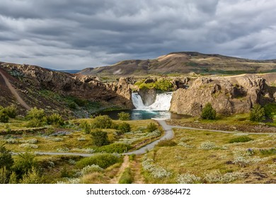 View of the Hjalparfoss waterfall under cloudy sky in Iceland.