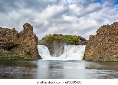 View of Hjalparfoss waterfall under cloudy sky in Iceland. Long exposure