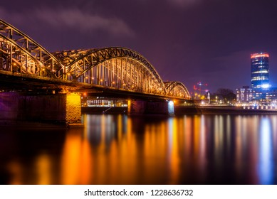 View of the Hohenzollern Bridge, the illuminated Skyscraper Cologne Triangle and the Long River Rhine (one of the longest Rivers in Europe) at Night in Cologne in 2018.