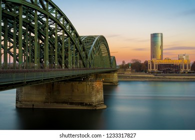 View of the Hohenzollern Bridge, the illuminated Skyscraper Cologne Triangle, the Hyatt Regency and the Long River Rhine (one of the longest Rivers in Europe) in the Evenin in Germany Cologne in 2018.