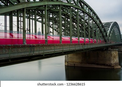 View of the Hohenzollern Bridge and a pink passing Train in Germany Cologne 2018.