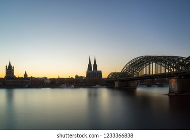 View of the Hohenzollernbridge, the Cologne Cathedral, the Groß St. Martin Church and the Long River Rhine in the Blue Hour in Germany Cologne 2018.