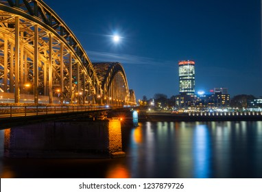 View of the Hohenzollernbridge, the Cologne Triangle, the Hyatt Regency and a beautiful bright Full Moon over the River Rhine at Night in Germany Cologne 2018.