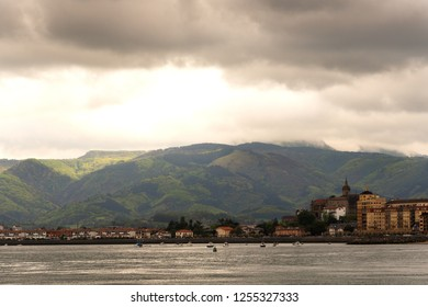 View of Hondarribia (Spain) marina, city buildings and Jaizkibel mountain at background in cloudy spring day with dramatic lighting.