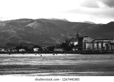 View of Hondarribia (Spain) marina, city buildings and Jaizkibel mountain at background in cloudy spring day. Black and white photo.