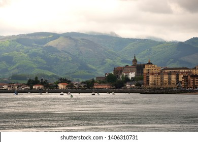 View of Hondarribia (Spain) marina, city buildings and Jaizkibel mountain at background in cloudy spring day.