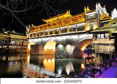 View of Hong bridge (Rainbow bridge) at night over the Tuojiang River (Tuo Jiang River) in Fenghuang old city (Phoenix Ancient Town),Hunan Province, China.