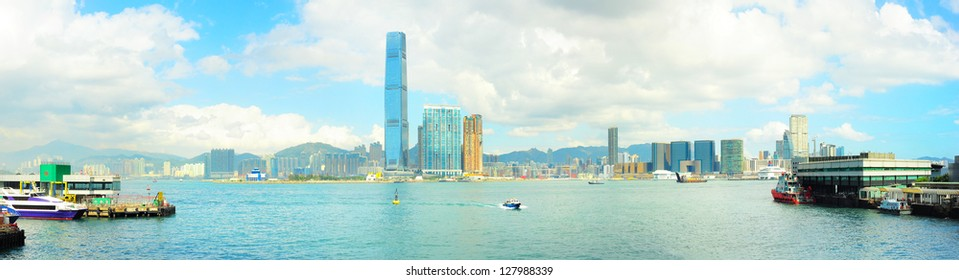 View from Hong Kong to Kowloon island in the sunshine day. Ferry piers on both side of picture.