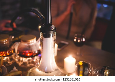 View of Hookah with candles and smoke on a table, hookah lounge with young people smoking in the background, shisha party club concept
