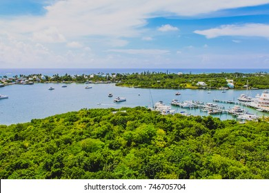 View of Hope Town harbour from the Elbow Reef Lighthouse with sailboats, yacht, the village, beautiful sky and Caribbean sea. Hope Town, Elbow Cay, Marsh Harbour, Abaco, Th Bahamas.