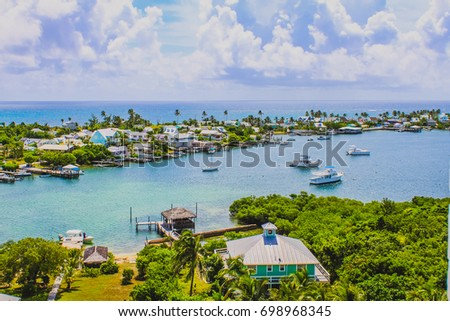 View of Hope Town harbour from the Elbow Reef lighthouse with sailboats, the village, beautiful sky and Caribbean Sea. Hope Town, Elbow Cay, Abaco, Bahamas