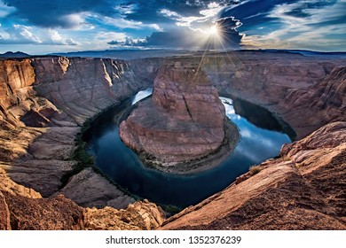 VIEW OF HORSESHOE BEND ON THE COLORADO RIVER WITH BACKLIT CLOUDS AND BLUE SKY AND SUNSTAR PEAKING OUT FROM BEHIND CLOUDS WITH SUNLIGHT STRIKING ROCKS IN FOREGROUND
