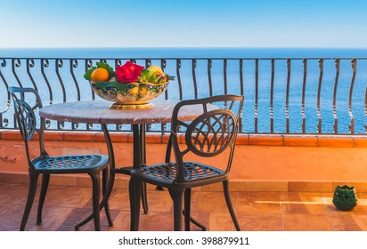 View from hotel room luxury and elegant mediterranean terrace with fruit and floewr bawl in morning sun, Sicily, Italy