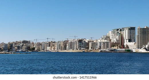 View of hotels and offices of Sliema region of Malta, taken from Sliema ferry crossing to Valletta. Blue sky and sea.