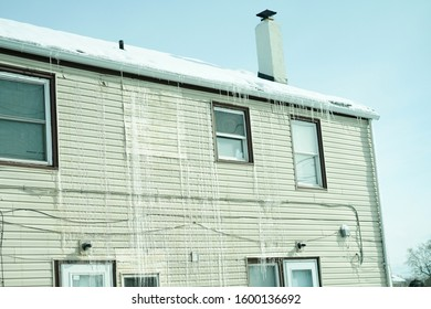 View of a house front side covered with ice created after melting of snow on the roof.