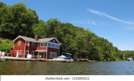 The view of a house from a kayak on a beautiful summer day.