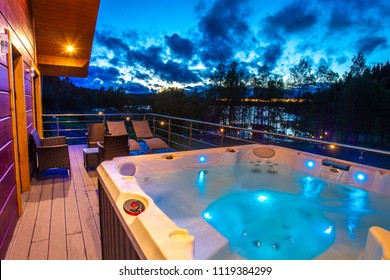 View from the house to the pool. Hydromassage. Pool on the balcony of the cottage. Jacuzzi on the background of the evening sky. Cottage with spa complex. House with pool.