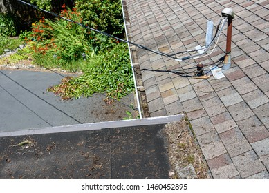 View from house rooftop of roof shingles, gutters, tree debris, moss, utility lines, driveway and garden