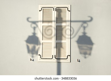 View of house wall with old-fashioned window shutter and streetlight shadow.