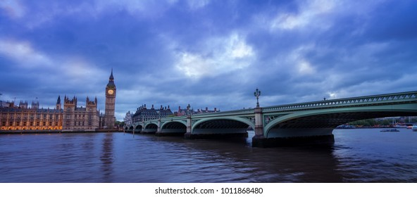 View of the Houses of Parliament and Westminster Bridge in London after dusk with dramatic sky