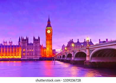 View of the Houses of Parliament and Westminster Bridge along River Thames in London at dusk.