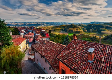 View of houses with tile roofs and autumnal hills of Roero on background in small town of Monticello d'Alba in Piedmont, Northern Italy.